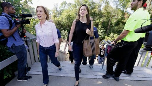 """In this photo taken Sept. 26, 2015, Republican presidential candidate Carly Fiorina walks with her assistant Rebecca Schieber, right, as they make their to talk with tailgaters before a University of Iowa football game in Iowa City, Iowa. Schieber has landed in a rare position on the presidential campaign trail, working as a """"body woman."""" The job isn't to provide to security, as the name implies, but rather to act as more of a personal assistant, adviser and sidekick."""