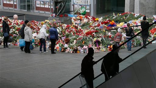 People stand near to floral tributes for the victims of a plane crash, at an entrance of Pulkovo airport outside St. Petersburg, Russia, Wednesday, Nov. 4, 2015. A Russian official says families have identified the bodies of 33 victims killed in Saturday's plane crash over Egypt. The Russian jet crashed over the Sinai Peninsula early Saturday, killing all 224 people on board. Most of them were holidaymakers from Russia's St. Petersburg. (AP Photo/Dmitry Lovetsky)