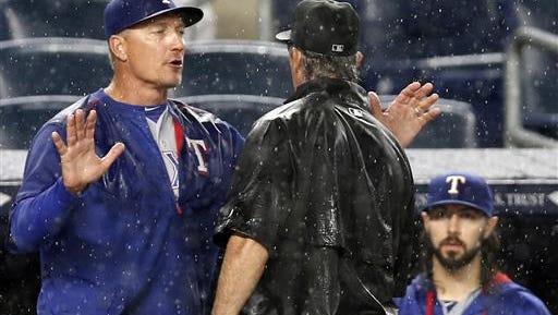 Texas Rangers manager Jeff Banister argues with crew chief Paul Nauert after umpires decided to call a rain delay with heavy rain falling in the ninth inning of a baseball game against the New York Yankees in New York, Monday.