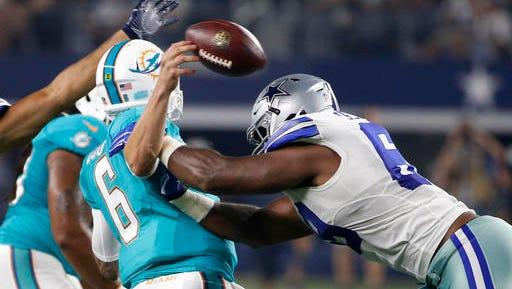 Miami Dolphins quarterback Brandon Doughty (6) fumbles the ball after being hit by Dallas Cowboys' Shaneil Jenkins in the first half of an NFL preseason football game.