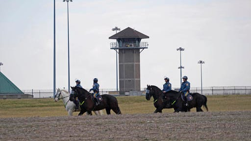 "Mounted police patrol travel along Smyrna Landing Road alongside James T. Vaugh Corrections center, Thursday, Feb. 2, 2017 in Smyrna, Del.   Inmates used ""sharp instruments"" to assume control of the building at the James T. Vaughn Correction Center on Wednesday, taking three prison guards and a woman counselor hostage."