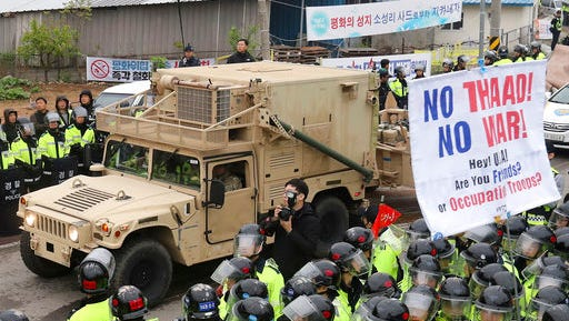 U.S. military vehicle moves past banners opposing a plan to deploy an advanced U.S. missile defense system called Terminal High-Altitude Area Defense, or THAAD, as South Korean police officers stand guard in Seongju, South Korea, Wednesday, April 26, 2017. South Korea says key parts of a contentious U.S. missile defense system have been installed a day after rival North Korea showed off its military power.