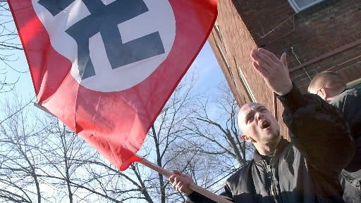 A neo-nazi carried a Nazi flag while taunting protesters during a white supremacist rally in York in January 2002.