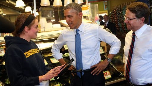 (L to R) Andrea Byl, a cashier at Zingerman's Deli in Ann Arbor, talks with President Obama and Rep. Gary Peters about the menu on April 2, 2014. Obama later spoke on the U-M campus.