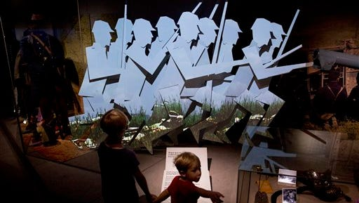 "Brothers Rafe, left, and Orlando Burley pose for photographers in front of an exhibit in the new ""First World War Galleries"" after major redevelopment works at the Imperial War Museum during a press preview event in London, Wednesday, July 16, 2014. The museum reopens Saturday after a six-month closure for a 40 million pound ($70 million) renovation timed to mark the centenary of World War I.  The museum was founded in 1917, as the war still raged, to preserve the stories of those who were fighting and dying. It retains that goal, as well its archaic name, relic of a long-gone British Empire."