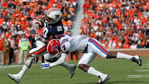 Auburn running back Corey Grant (20) is tackled by Louisiana Tech defensive back Xavier Woods (7) during the first half of an NCAA college football game Saturday, Sept. 27, 2014, in Auburn, Ala. (AP Photo/Brynn Anderson)