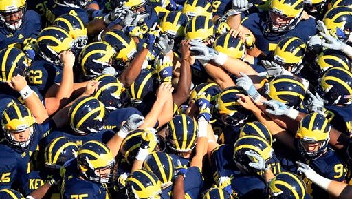 The Michigan football team huddle before the first quarter of an NCAA college football game against Massachusetts at Michigan Stadium in Ann Arbor, Mich., Saturday, Sept. 15, 2012. (AP Photo/Carlos Osorio)