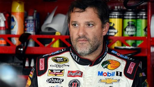 n this Sept. 13, 2014, file photo, NASCAR driver Tony Stewart (14) looks out from his garage. Stewart will not face criminal charges in Kevin Ward Jr.'s death, a grand jury in upstate New York decided.