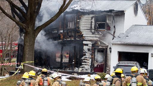 Firefighters stand outside a house in Gaithersbug, Md. on Monday, where a small plane crashed. A small, private jet has crashed into a house in Maryland's Montgomery County, and a fire official says at least three people on board were killed.