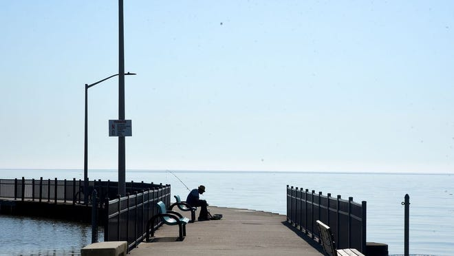 An angler baits his lines before fishing in May at Evans Pier in Luna Pier.