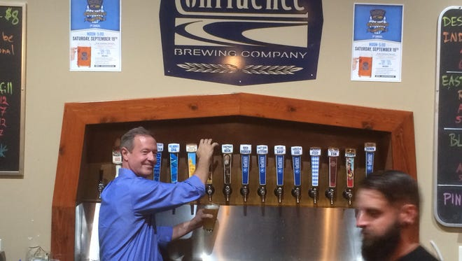 Martin O'Malley pours a pint before speaking to a standing-room-only crowd at Confluence Brewing Company.