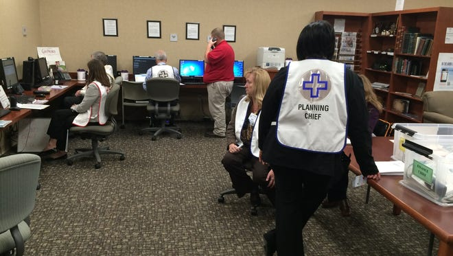 Reid Health employees staff the operations room during a practice disaster scenario Monday.