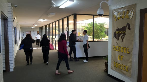 Tejas School of Choice students walk by the school