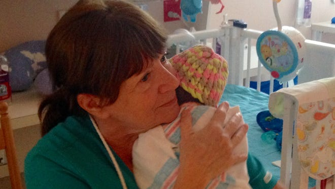 """Julia Wellman, a volunteer baby """"cuddler"""" at the Golisano Children's Hospital of Southwest Florida, comforts a baby suffering the effects of drug withdrawal, a condition known as neonatal abstinence syndrome."""