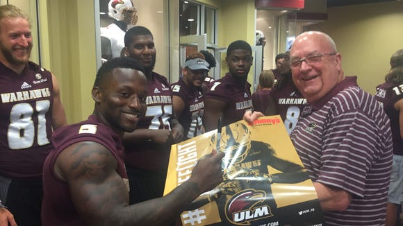 Tyler Cain (5) and several ULM players sign autographs