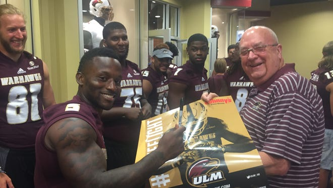 """Tyler Cain (5) and several ULM players sign autographs for fans at football program's """"Meet The Team"""" night on Friday."""