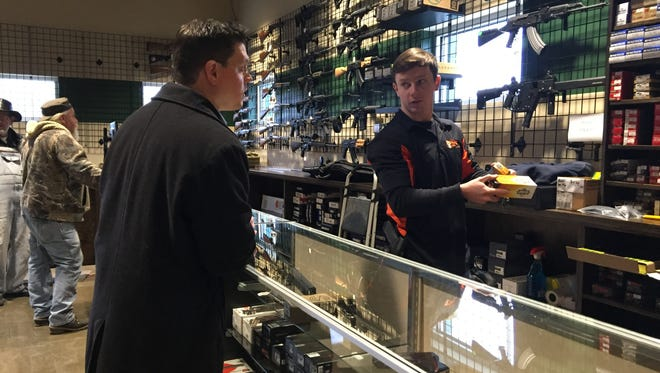 Greg Cottrill of Ohio Means Jobs talks to Charlie Marcks about merchandise following the grand opening of the new Hammer Down Range in Goshen Township.