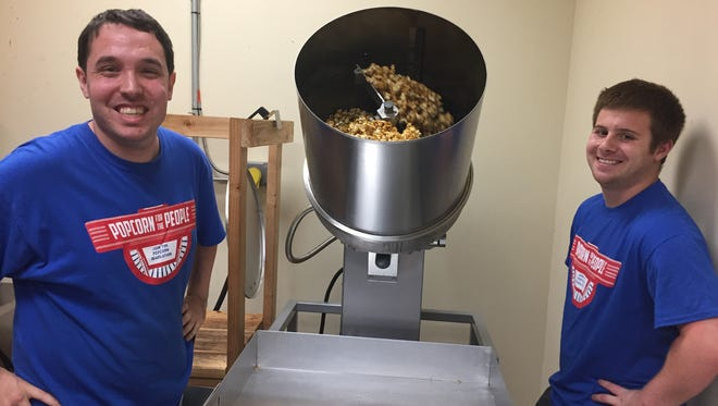 Popcorn For The People employee Joseph DiPaola of Somerset works the caramelizer with Disability Allies Life Coach Alex Gallo at the new headquarters of the organization. Popcorn For The People officially opened the new headquarters on Harts Lane on Wednesday.