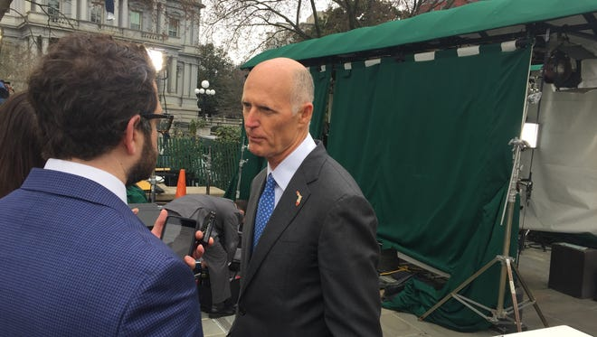 Florida GOP Gov. Rick Scott speaks with reporters outside the White House Monday following a meeting with President Trump.
