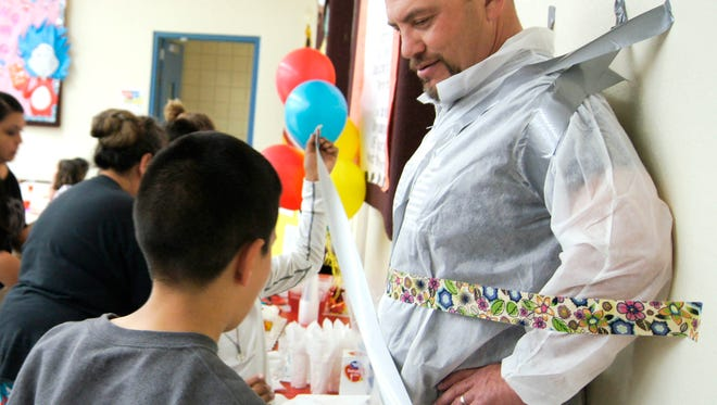 Students who scored 100 points on their reading exams, which follow books they have read, get to duct tape Principal Louis Alvarez to the cafeteria wall on Wednesday at Sixth Street Elementary School in Silver City.
