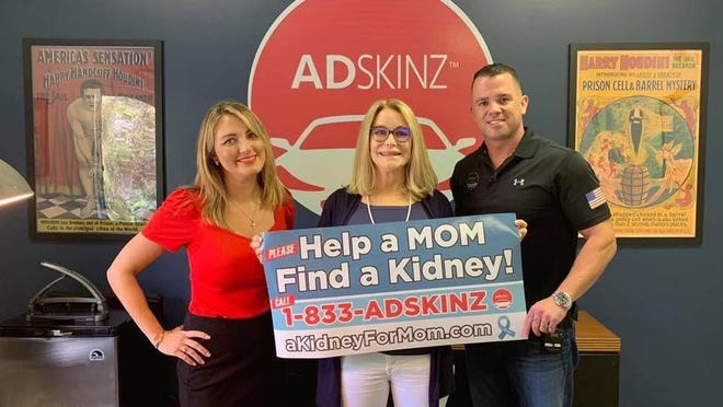 ADSKINZ founder Jason Mariner (right), with his wife, Charlene (left), and  kidney recipient Corinne Ghelber of Boca Raton, display the ad placed on the back of a car that helped publicize Ghelber's search for a new kidney. The ad attracted the attention of a Davie resident who is poised to become a donor for a Tequesta man battling kidney disease.