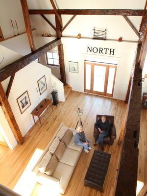 Carole and Jerry Damon are photographed from the second floor of their barn-based home in Cohoctah Township. The structure was moved from its original site 900 feet away, then refurbished using much of the original materials to create an eclectic mix of Shaker and modern style with high ceilings throughout.