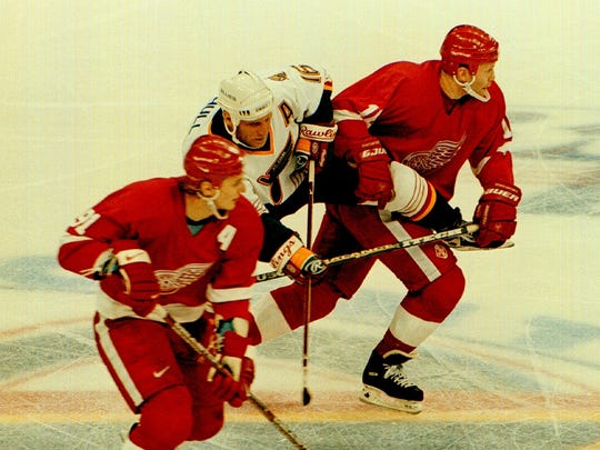 Brett Hull of the St. Louis Blues tries to check Vladimir Konstantinov (16) of the Detroit Red Wings during the game as teammate Sergei Fedorov skates by at the Kiel Center in St. Louis on April 20, 1997.