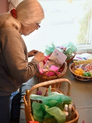 Mary White-Levilain assembles baskets for the upcoming Central Minnesota Women Shine Spring Into Windows fundraiser March 31 at the Red Carpet Martini Lounge in St. Cloud.