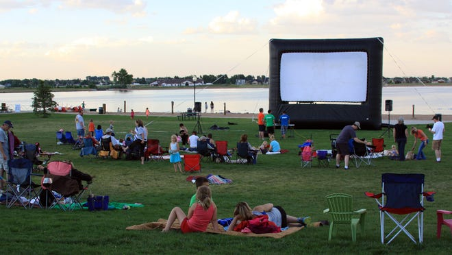Crowds relax while waiting for the movie to start Friday evening at Boardwalk Park. Residents are invited to bring blankets or lawn chairs to watch the free movies Friday nights.