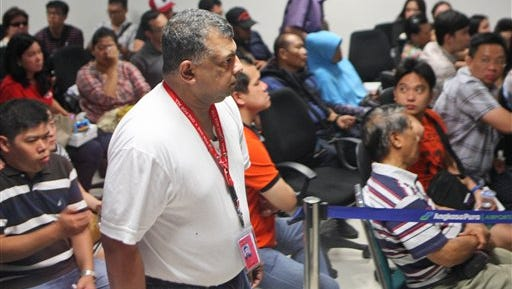 AirAsia Group CEO Tony Fernandes, center, walks past the relatives of the passengers of AirAsia flight QZ8015 at Juanda International Airport in Surabaya, East Java, Indonesia, on Sunday. A massive sea search was underway for the AirAsia plane that disappeared Sunday while flying from Indonesia to Singapore through airspace possibly thick with dense storm clouds, strong winds and lightning, officials said.
