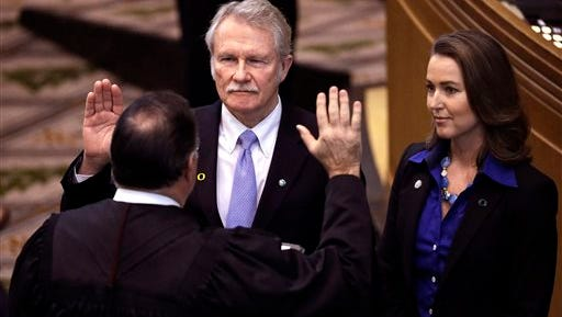 In this Jan. 12, 2015, file photo, Oregon Gov. John Kitzhaber, center, is joined by his fiancee, Cylvia Hayes, as he is sworn in for an unprecedented fourth term by Senior Judge Paul J. De Muniz in Salem, Ore. After seeing Kitzhaber resign under pressure, Oregon voters may be deciding whether state legislators should have power to impeach elected officials from the executive branch. A state House resolution approved Tuesday, May 19, 2015, would send a proposed state constitutional amendment to the ballot in 2016. Oregon is the only state without a legislative impeachment process.   (AP Photo/Don Ryan, File)