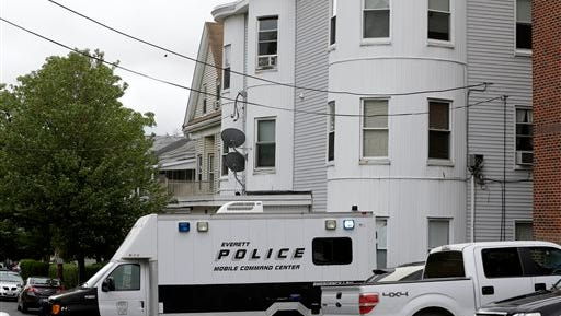 Police vehicles sit in front of a multi-storied home Tuesday, June 2, 2015, in Everett, Mass., being searched by authorities in connection with a man shot and killed earlier in the day in Boston.  The man, under surveillance by terrorism investigators, was killed after he lunged with a knife at a Boston police officer and an FBI agent, Boston police Commissioner William Evans said. (AP Photo/Steven Senne)