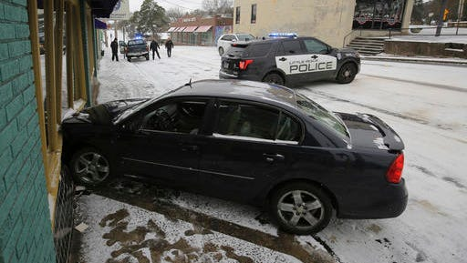 Little Rock police work the scene of an accident where a car struck the Oyster Bar restaurant along an icy W. Markham Street Friday morning, Jan. 6, 2017 in Little Rock..
