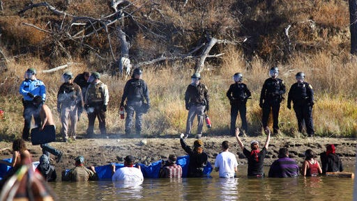 FILE - In this Nov. 2, 2016, file photo, protesters demonstrating against the expansion of the Dakota Access pipeline wade in cold creek waters confronting local police near Cannon Ball, N.D. North Dakota officials appear poised to go after the U.S. government — and thus U.S. taxpayers — to recoup more than $38 million in state expenses related to months of protests against the Dakota Access pipeline.