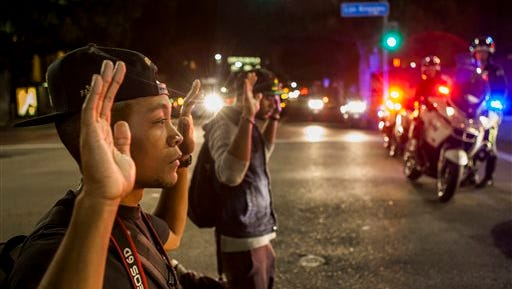 In this Nov. 26, 2014 photo, protesters kneel down with their hands up in front of Los Angeles police officers in downtown Los Angeles. 'Hands Up, Don't Shoot' has become a rallying cry despite questions whether Michael Brown's hands were raised in surrender before being fatally shot by a Ferguson police officer.