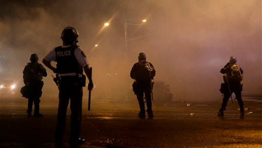 A law enforcement officer watches Sunday, Aug. 17, 2014, as tear gas is fired to disperse a crowd protesting the shooting of teenager Michael Brown last Saturday in Ferguson, Mo. Brown's shooting in the middle of a street following a suspected robbery of a box of cigars from a nearby market has sparked a week of protests, riots and looting in the St. Louis suburb. (AP Photo/Charlie Riedel)