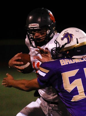 Aztec quarterback Cody Smith stiff arms Kirtland Central's Jonathan Arreola during Friday's game at Bronco Stadium in Kirtland.