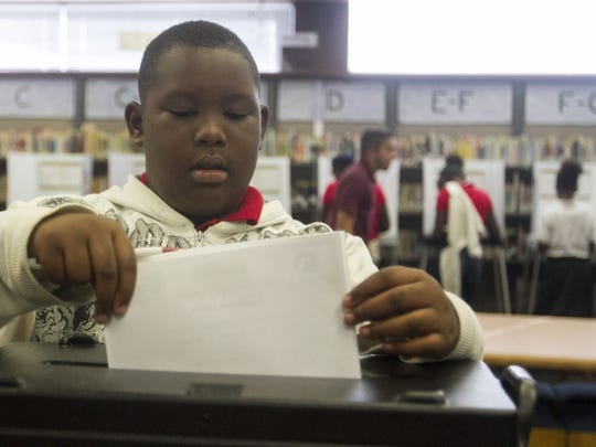 Colonial Elementary School fifth grader Zabeian Isom submits his ballot for President of the United States in the school's mock election on Thursday in Fort Myers.