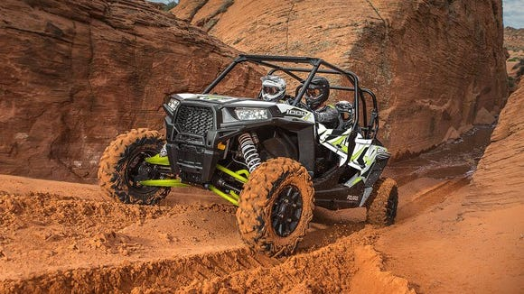 Polaris RZR 1000 driving through a dirt canyon