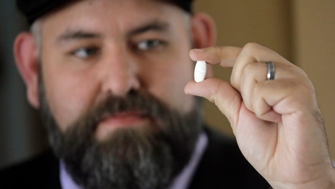 Jake Martinez, 32, looks at his medication at his home Thursday, May 4, 2017, in Murray, Utah. Martinez, who has epilepsy, is worried about health insurance as Republicans move closer to dismantling the Obama health care system, known as the Affordable Care Act, which he and his wife use. (AP Photo/Rick Bowmer)