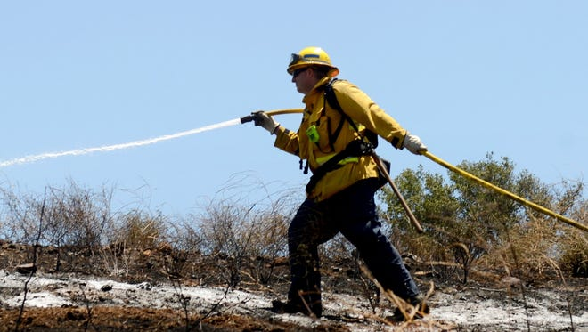 Ryan Osler, of the Ventura County Fire Department, hoses down a fire in Thousand Oaks in July. He died last week in a Lompoc vehicle accident.