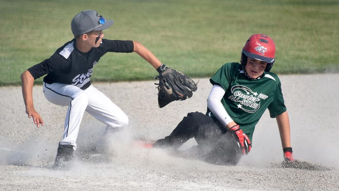 Custer's Noah Miller slides into third base for a triple as Nate Miller of Ida waited for the throw in the 2017 Monroe County Fair Tournament.