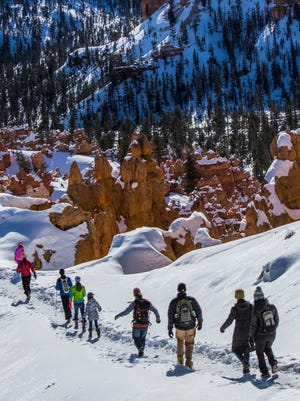 A family goes for a hike at Bryce Canyon National Park, Sunday, Jan. 17, 2016.