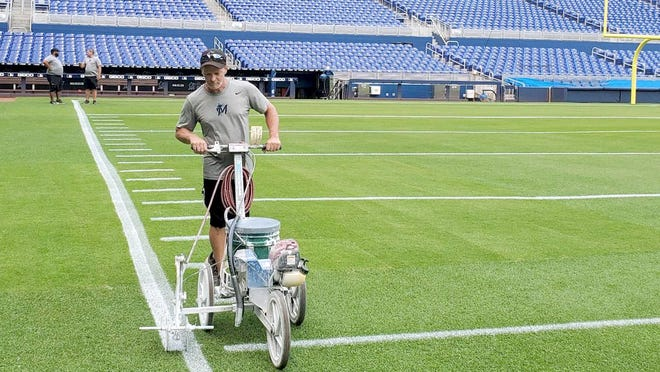 Former Veterans Memorial Park groundskeeper Tom Campione, a Little Falls native, applies paint to the football sideline while he and the rest of the Miami Marlins' grounds crew were preparing Marlins Park for a game between Florida International University and the University of Miami last November.