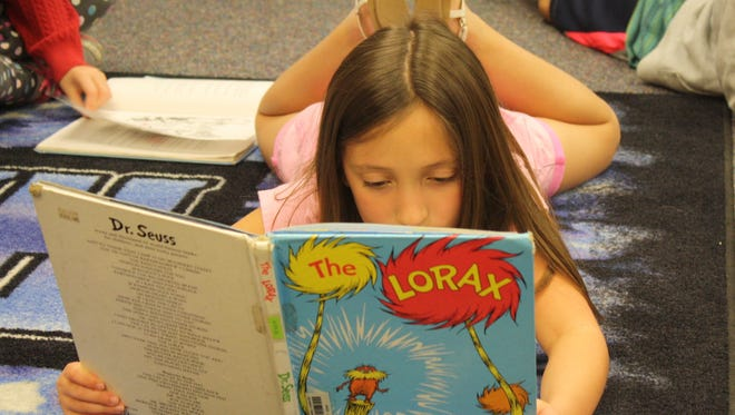 """A students kicks her feet up in the Lewis Carroll Elementary library to read one of Dr. Seuss' most famous books, """"The Lorax."""""""