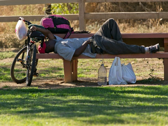 A cyclist lays down in the shade on a bench in Griffith