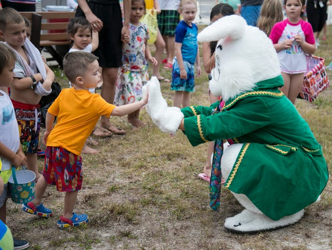 The Easter bunny greets children before the egg hunt