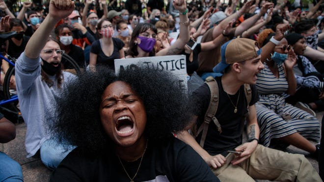 "Ebri Yahloe, 26, of Columbus, chants ""No Justice, No Peace"" while sitting along High Street as protests continue following the death of Minneapolis resident George Floyd on Monday, June 1, 2020 in Columbus, Ohio. Floyd, a 46-year-old black man, was killed while in police custody after allegedly passing a counterfeit $20 bill at a conveinence store. Derek Chauvin, one of four Minneapolis police officers involved in Floyd's arrest, has himself been arrested and charged with third-degree murder and manslaughter. During the arrest, video footage showed Chauvin kneeling on Floyd's neck for almost nine minutes as Floyd repeatedly said ""I can't breathe."""