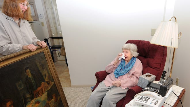 Eileen Kestly is filled with emotion as her daughter, Mary Brittnacher, presents her with a long lost painting. Eileen had spotted the painting in a newspaper photo and thinks it used to hang in her childhood home.