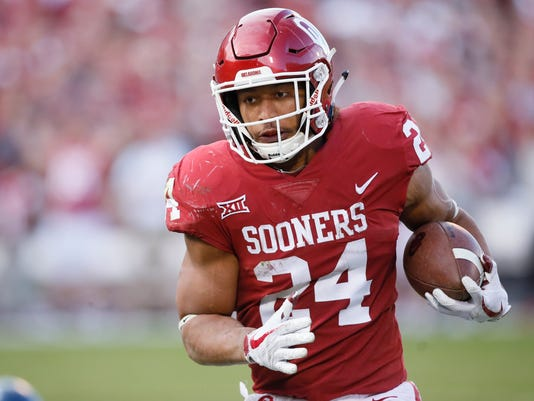 FILE - In this Nov. 25, 2017, file photo, Oklahoma running back Rodney Anderson (24) carries the ball in the second quarter of an NCAA college football game against West Virginia in Norman, Okla. Anderson will not be charged after a woman accused him of sexual assault, Cleveland County District Attorney Greg Mashburn said Thursday, Dec. 14, 2017. The accusation stemmed from a petition for a protective order in which the woman said Anderson assaulted her in her apartment and that she feared for her safety.  (AP Photo/Sue Ogrocki, File)